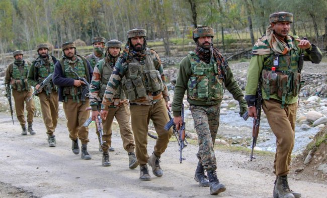 Army soldiers walk towards the house where top Hizbul Mujahideen commanders were hiding during an encounter in which PhD scholar-turned-militant Mannan Wani was killed, in Handwara.(PTI photo)