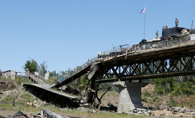 Local residents cross a bridge, which was exploded during a military conflict on the contact line between forces of the separatist Luhansk People\'s Republic and Ukrainian armed forces, as members of the self-proclaimed republic\'s emergencies ministry dismantle fortifications in Stanytsia Luhanska settlement, Ukraine August 26, 2019. (REUTERS/Alexander Ermochenko)