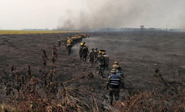 Firemen walk through a burnt field as they combat a fire in the surroundings of Robore in eastern Bolivia, on August 22, 2019. (STR / AFP)