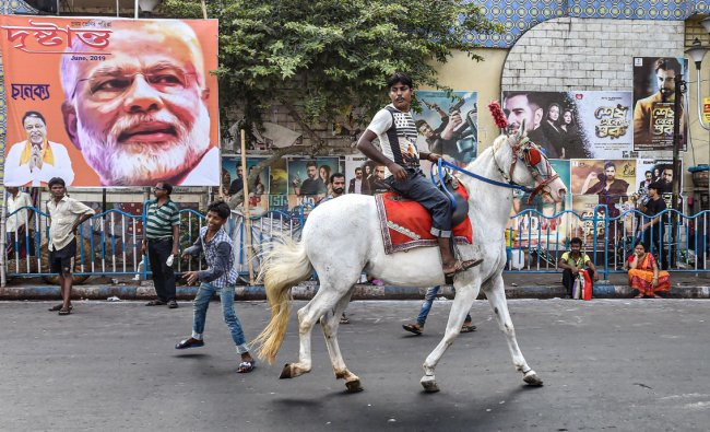 A man rides a horse in the backdrop of a poster depicting prime minister Narendra Modi and BJP leader Mukul Roy, in Kolkata, Monday, June 10, 2019. (PTI Photo/Ashok Bhaumik)