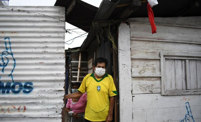 A man stands at his door, where he has hung a white and a red flag as a signal he needs to be delivered food (white) and medicines (red), at La Brigada neighbourhood in Guatemala City. (AFP Photo)