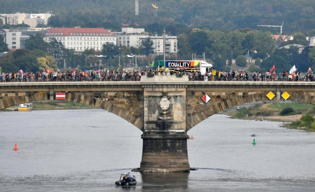 People walk on a bridge over the river Elbe as they take part in a demonstration titled \