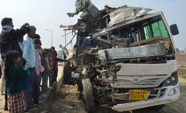 People look on at a mangled tourist bus which collided with a truck on Sitamarhi-Muzaffarpur NH-77, in Sitamarhi. PTI photo