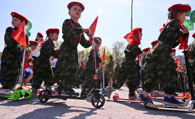 Children wearing military uniform ride kick scooters during a parade, held by Russian servicemen, pupils of infant and primary schools, which is a public event to honour World War Two veterans and to mark the upcoming Victory Day, in Rostov-on-Don, Russia April 25, 2019. REUTERS/Sergey Pivovarov