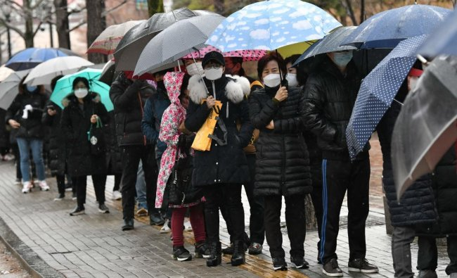 People wait in a line to buy face masks at a retail store in the southeastern city of Daegu. (AFP Photo)