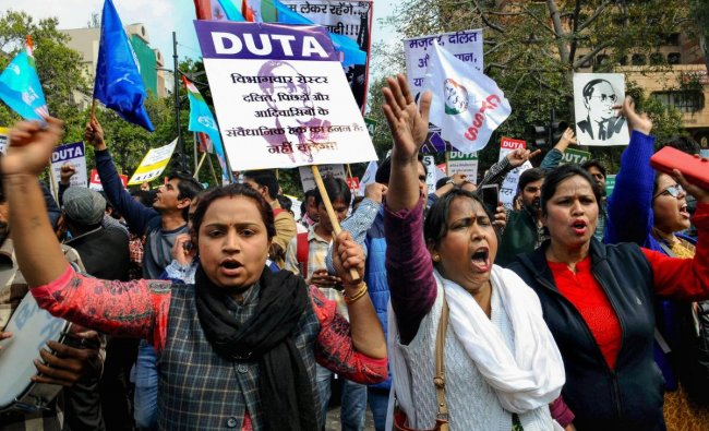 Members of the Delhi University Teacher\'s Association (DUTA) along with students from several Universities stage a protest against the \'13-point roster system\' at Jantar Mantar. PTI