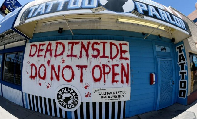 A sign posted outside Wolfpack Tattoo Las Vegas reads \