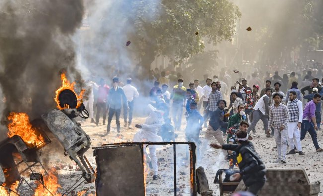 Vehicles set ablaze as protestors throw brick-bats during clashes between a group of anti-CAA protestors and supporters of the new citizenship act, at Jafrabad in North East Delhi. (PTI Photo)