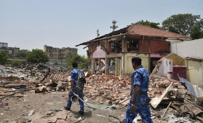Security personnel make way through the debris of demolition structures at the British-era Gole Market, in Patna, Sunday, June 16, 2019. Gole Market is Patna\'s first planned municipal market that was built over 100 years ago. PTI