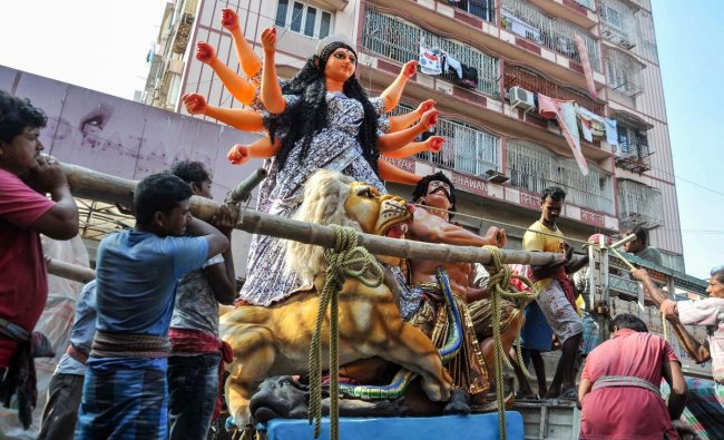 People carry Lord Durga idol to a pandal for installation ahead of Durga Puja festival, in Kolkata on Friday. PTI photo
