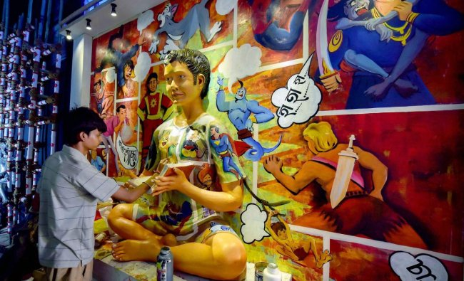 An artist paints a model at a puja pandal themed \'Remembering Childhood\' ahead of Durga puja festival, in Kolkata on Saturday.(PTI Photo)