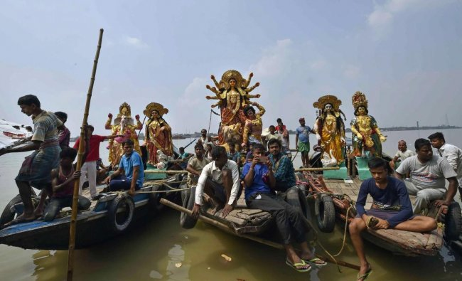 People carry idols of Goddess Durga across River Ganga to install at pandals for the upcoming Durga Puja festival, in Kolkata on Sunday. (PTI Photo)