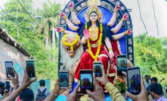 Devotees carry an idol of Goddess Durga for installation at a puja pandal as ther take photos on their mobile phones, on the eve of Navratri festival, in Bhopal. (PTI photo)