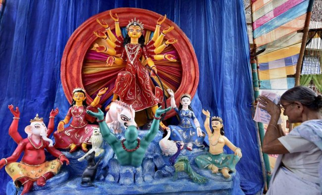 An elderly woman offers prayers in front of an idol of Goddess Durga at a puja pandal, in Kolkata. (PTI photo)