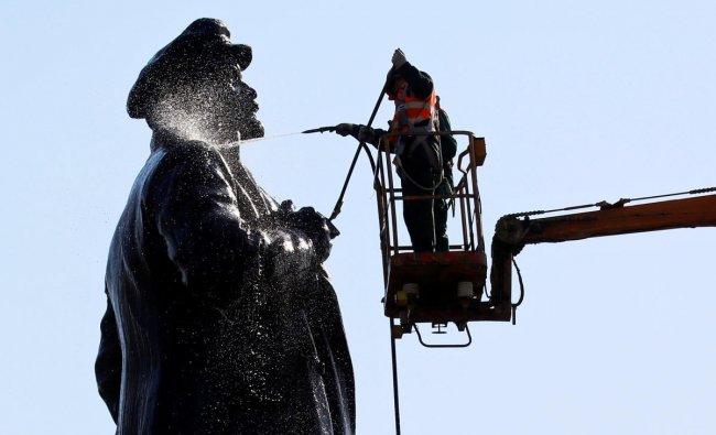 Employees of a public utility wash a monument to Soviet state founder Vladimir Lenin in Krasnoyarsk, Russia April 25, 2019. REUTERS/Ilya Naymushin