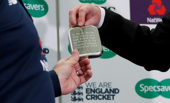 England head coach Trevor Bayliss is presented a hip flask by George Dobell during the press conference. (Photo by Reuters)