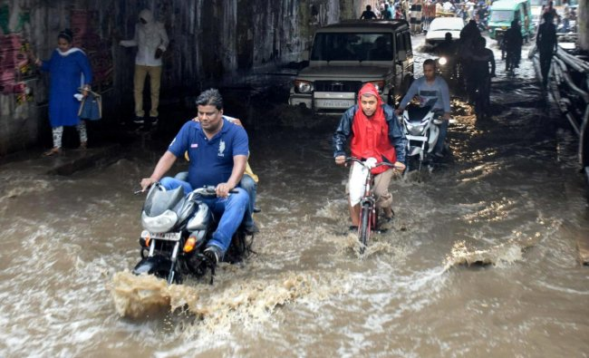 Commuters ride on a road during a heavy rainfall, in Allahabad on Sunday. PTI Photo