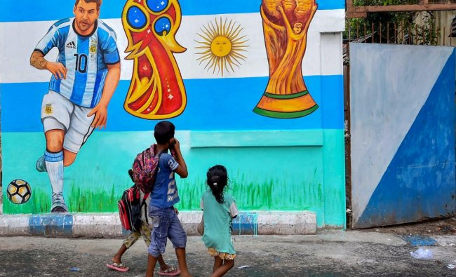 Children walk past a wall graffiti of Argentine footballer Lionel Messi as FIFA fever grips various parts of the country, in Kolkata on Thursday. PTI Photo