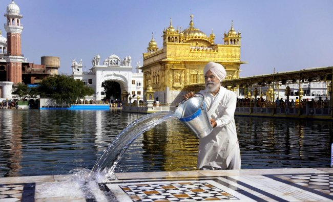 A Sikh volunteer pours water on the marble floor surrounding Harmandir Sahib (Golden Temple) to keep it cool on a hot, summer day in Amritsar on Thursday. PTI Photo