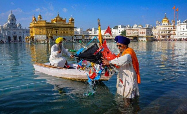 A sewadar takes out kites as he cleans the sarovar at Sri Harmandir Sahib (Golden Temple) on the birth anniversary of tenth Sikh guru, Guru Gobind Singh Ji, in Amritsar. PTI photo
