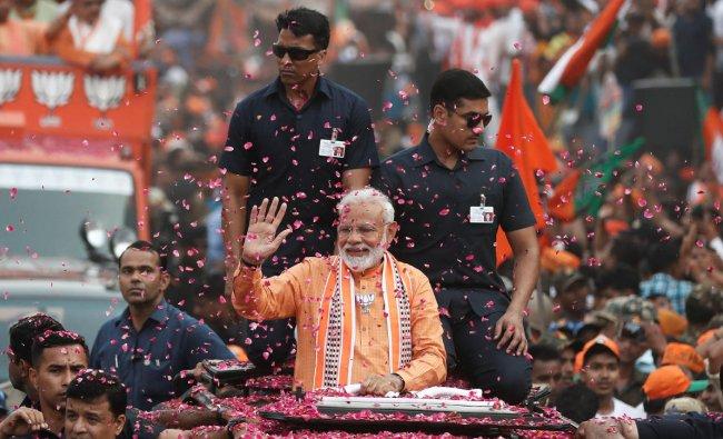India\'s Prime Minister Narendra Modi waves towards his supporters during a roadshow in Varanasi, India, April 25, 2019. REUTERS/Adnan Abidi