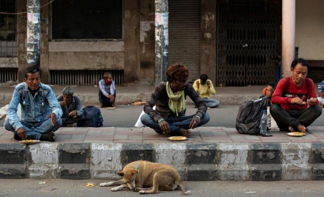 Daily wage labourers and homeless people eat food distibuted by a non-governmental organisation in New Delhi. (Reuters photo)
