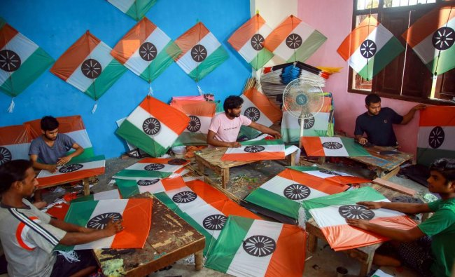 Kite makers busy in making tri-coloured kites at a workshop, ahead of the Independence Day celebrations, in Jammu on Thursday. PTI photo