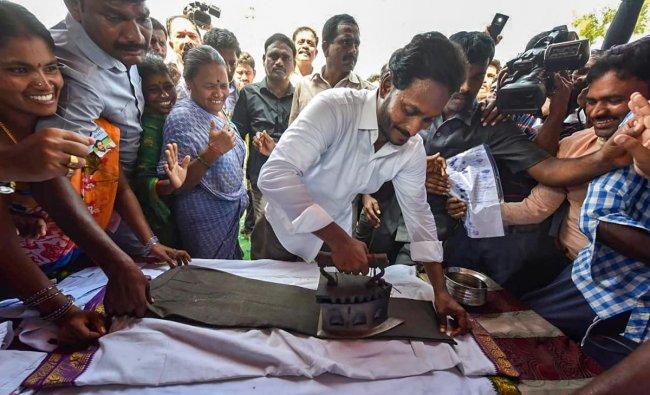YSR Congress Party President Y S Jaganmohan Reddy irons clothes at a shop during his \'Praja Sankalpa Yatra\' in Cheepurupally constituency of Vizianagaram district. (PTI photo)