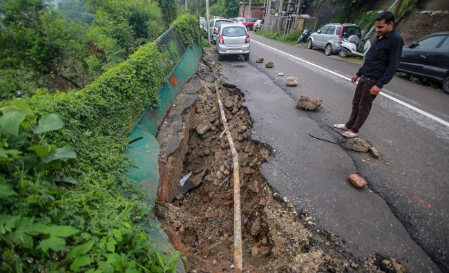 A person looks on at a caved road following monsoon rainfall, in Jammu on Monday. PTI Photo