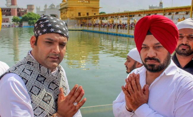 Indian comedian Kapil Sharma and Gurpreet Ghuggi offer prayers at Golden Temple during a promotion for their upcoming film \