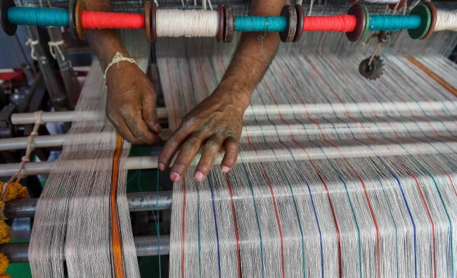 An artisan demonstrates the functioning of mechanised manual loom at a stall at the Khadi Utsav, organised by Khadi and Village Industries Commission on the occasion of 150th Birth Anniversary celebrations of Mahatma Gandhi, in Bengaluru. PTI