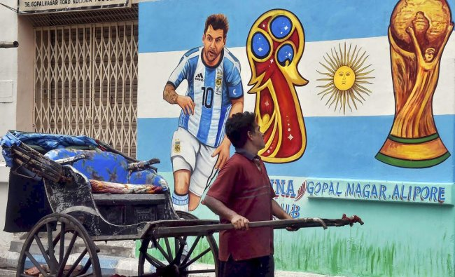 A hand-rickshaw puller moves past a wall painted with graffiti of Argentine footballer Lionel Messi ahead of FIFA World Cup 2018, in Kolkata on Sunday.PTI Photo