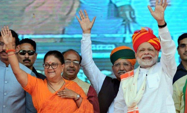 Prime Minister Narendra Modi and Rajasthan Chief Minister Vasundhara Raje greet their supporters during \'Vijay Sankalp Sabha\' in Ajmer on Saturday. (PTI Photo)