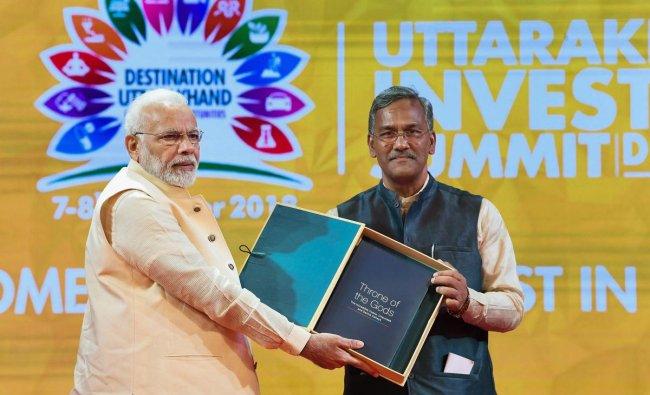 Prime Minister Narendra Modi being presented a memento by Chief Minister Trivendra Singh Rawat at the 1st Uttarakhand Investors Summit 2018, in Dehradun, Uttarakhand on Sunday. (PTI Photo)