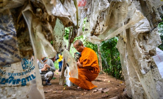 A Buddhist monk sits next to used plastic bags at Khung Bang Kachao Urban Forest and beach collected as part of the Trash Hero initiative in Bangkok on August 25, 2019. (Photo by Mladen ANTONOV / AFP)