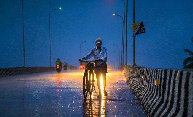 Kanyakumari: A man walks along a road with his bicycle during pre-Monsoon showers at Nagercoil in Kanyakumari district, Monday, June 10, 2019. (PTI Photo)