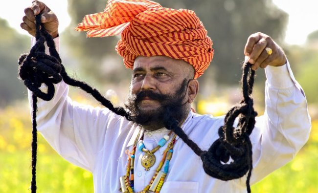 Girdhar Vyas, who claims to have the longest (26 ft) moustaches in the world at a mustard field, in Bikaner. PTI