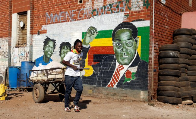 A youth pushes a cart loaded with maize for sale nearby a mural depicting Zimbabwe\'s former President Robert Mugabe, after hearing the news of his death, in Mbare in the capital Harare, Zimbabwe, September 6, 2019. REUTERS/Philimon Bulawayo