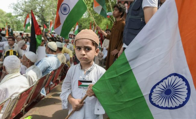 A Child holds a tricolour during a protest organized by Majlis-e-Ulama-e-Hind in solidarity with Palestinian people and demanded the liberation of Jerusalem\'s holy Al-Aqsa Mosque, at Jantar Mantar, in New Delhi, on Friday. PTI Photo