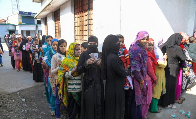Muslim women stand in a long queue to cast their votes for local body elections in Dehradun, Sunday. PTI photo