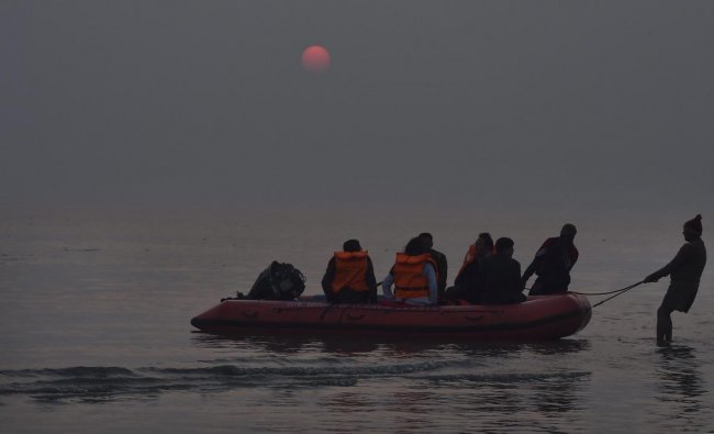 NDRF team return during sunset after their day long vigil, in Sagar Island, Kolkata on Sunday. PTI photo