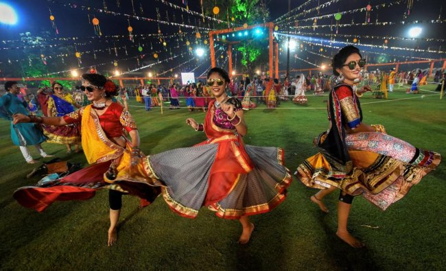 Youngsters dressed in traditional attire participate in the traditional folk dance \'Garba\' on the first day of nine-day Navratri festival, in Ahmedabad. (PTI photo)