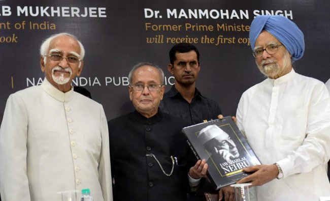 Former prime minister Manmohan Singh receives the first copy of the book from former president Pranab Mukherjee as former vice president Hamid Ansari looks on, during the book launch of \'Jawaharlal Nehru\' an illustrated biography by A Gopanna, in New Delhi, on Sunday. PTI Photo