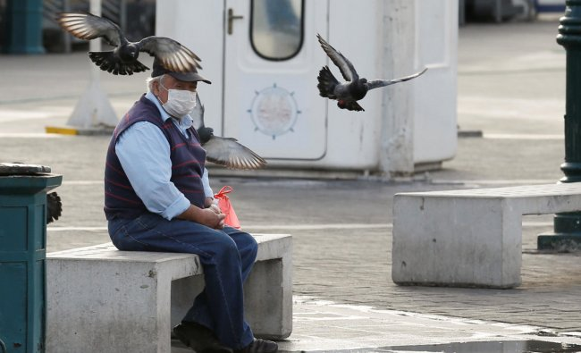 A man wearing a protective face mask as a precaution against the spread of the coronavirus disease (COVID-19) rests in a public square in Valparaiso, Chile. (Reuters photo)