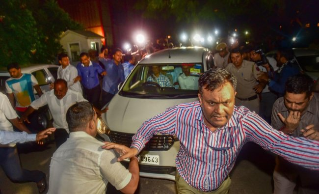 An official clears the way for the vehicle in which Central Bureau of Investigation (CBI) officials escorted Congress leader P Chidambaram after his arrest from his Jor Bagh residence in New Delhi, Wednesday, Aug 21, 2019.