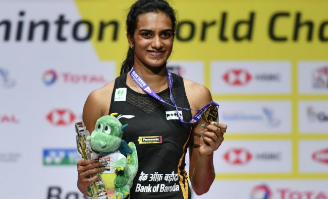 India\'s PV Sindhu poses with the gold medal during the podium cermony after her victory over Japan\'s Nozomi Okuhara during their women\'s singles final match at the BWF Badminton World Championships at the St Jakobshalle in Basel on August 25, 2019. (Photo by FABRICE COFFRINI / AFP)