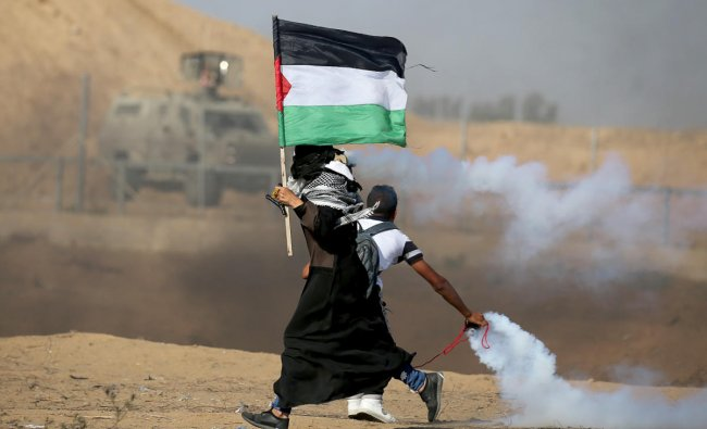A woman holding a Palestinian flag runs as tear gas fired by Israeli forces during an-anti Israel protest, at the Israel-Gaza border fence in the southern Gaza Strip on August 23, 2019. (REUTERS/Ibraheem Abu Mustafa)