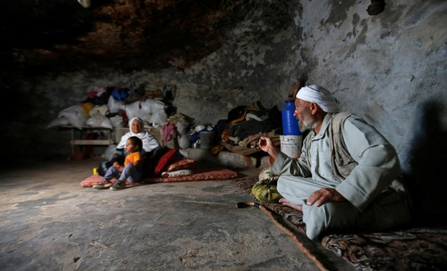Members of a Palestinian family sit in a cave they live in, near Yatta in the Israeli-occupied West Bank. (REUTERS/Mussa Qawasma)