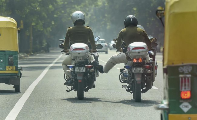A police man helps push his colleague\'s non-working motorcycle. PTI