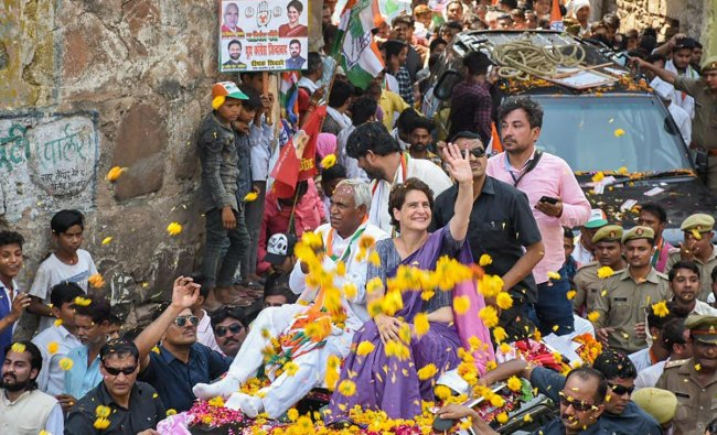 Congress General Secretary Priyanka Gandhi Vadra waves at the supporters during an election campaign roadshow in support of the party candidate Shiv Sharan Kushwaha(to Priyanka\'s right) for the Lok Sabha elections, in Jhansi, Thursday, April 25, 2019. (PTI Photo)